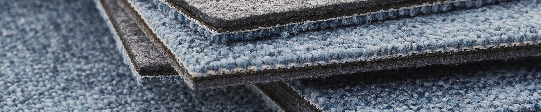 Stack of carpet tiles showcasing the acoustic felt underlay of DESSO SoundMaster